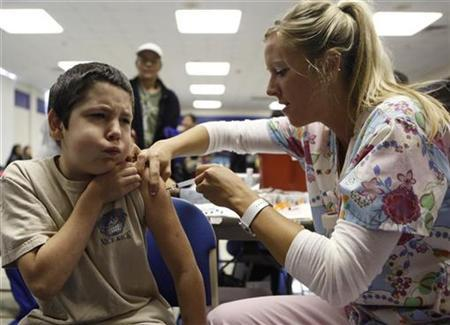 Anthony Adams, 10, reacts as nurse Fawna Dougoud administers his shot of the H1N1 vaccine in Haltom City, Texas October 30, 2009. REUTERS/Jessica Rinaldi