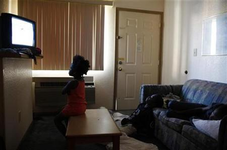 Children watch television inside a motel room in Grand Prairie, Texas July 2, 2009. REUTERS/Jessica Rinaldi