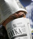 """<p>Сторонник оппозиции закрывает лицо газетой """"Республика"""" на митинге в Алма-ате 24 июня 2006 года. Финансовая полиция Казахстана возбудила уголовное дело в отношении директора типографии, сотрудничавшей с оппозицией, обвинив Юлию Козлову в искажении бухгалтерской отчетности. REUTERS/Shamil Zhumatov</p>"""