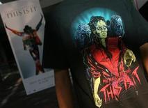 <p>Fã mostra estampa de camisa do Michael Jackson em cinema onde está sendo exibido o longa This Is It, em Mumbai.Filme sobre Michael Jackson supera US$ 144 milhões no mundo.REUTERS/Arko Datta</p>