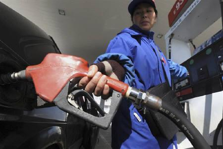 An employee fills a vehicle at a gas station in Hefei, Anhui province January 1, 2009. REUTERS/Jianan Yu/Files