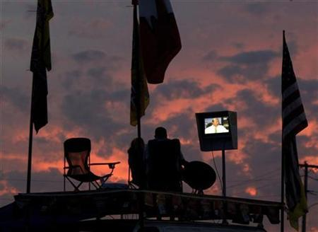 Eric Bonham and his sister Samantha Bonham, from Ft Myers, Florida, watch racing on their television atop their van in the infield area of Daytona International Speedway as Speed Week heats up in Daytona Beach, Florida February 11, 2009. REUTERS/Mark Wallheiser