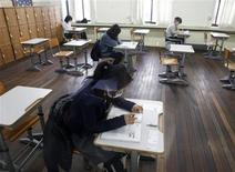 <p>Examinees who have a high fever, wait before they take a college entrance exam at a separate exam hall in Seoul November 12, 2009. REUTERS/Lee Jae-Won</p>