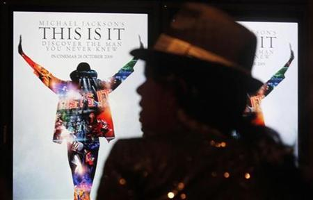 A Michael Jackson fan waits next to electronic posters at the Australian premiere of the documentary ''This Is It'', in Sydney October 28, 2009. REUTERS/Daniel Munoz