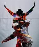 """<p>Artista faz pose diante de cartaz do filme """"This Is It"""", em Taipei. """"This Is It"""", filme que mostra os últimos ensaios da carreira de Michael Jackson, superou os 200 milhões de dólares nas bilheterias do mundo duas semanas depois da estreia, disse o estúdio responsável pelo lançamento na quinta-feira.28/10/2009.REUTERS/Nicky Loh</p>"""