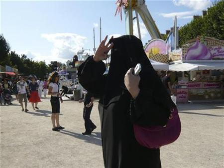 A woman wearing a niqab walks in the Tuileries Garden in Paris July 25, 2009. REUTERS/Sandra Auger