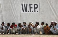 <p>Persone in fuga da un'offensiva militare in Waziristan, in coda per il cibo sotto il logo del Pam, Programma alimentare mondiale. (In inglese Wfp) REUTERS/Akhta Soomro</p>