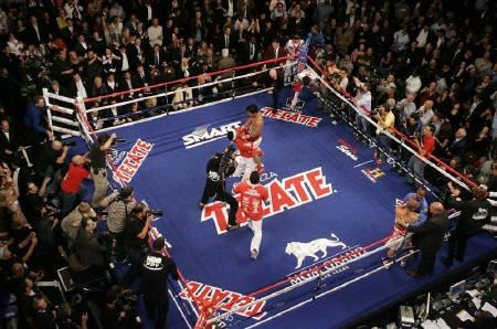 Manny Pacquiao (C) of the Philippines is lifted up by Filipino trainer Buboy Fernandez after beating Miguel Cotto of Puerto Rico in the 12th round to win the WBO welterweight title at the MGM Grand Garden Arena in Las Vegas, Nevada November 14, 2009. REUTERS/Steve Marcus