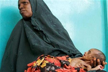 A Somali woman holds her malnourished child along the corridors at Banadir hospital in the capital Mogadishu, August 10, 2009. REUTERS/Ismail Taxta