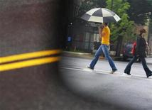 <p>Pedestrians are reflected in the side mirror of a car as they walk across a street in Boston, Massachusetts July 1, 2009. REUTERS/Brian Snyder</p>