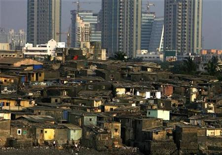 High rise buildings are seen behind a slum in Mumbai April 28, 2009. REUTERS/Arko Datta