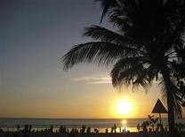 <p>Beachgoers watch the sun set at Kuta beach in Bali, Indonesia August 24, 2009. REUTERS/Sharon Lee</p>