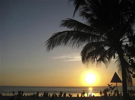Beachgoers watch the sun set at Kuta beach in Bali, Indonesia August 24, 2009. REUTERS/Sharon Lee