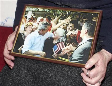Thomaidha Kaziu, 70, holds a picture showing her meeting with U.S. President George W. Bush in the Albanian town of Fushe-Kruje January 17, 2009. REUTERS/Arben Celi