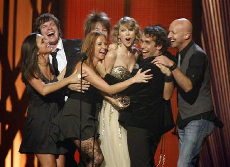 Singer Taylor Swift (C) is surrounded by members of her band as she accepts the Entertainer of the Year award onstage at the 43rd annual Country Music Association Awards in Nashville November 11, 2009.   REUTERS/Tami Chappell/Files