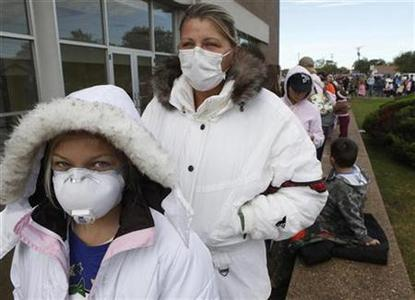 Allene Diaz (L), 11, and her mother, Christina, wait in line for the H1N1 vaccine in Haltom City, Texas October 30, 2009. REUTERS/Jessica Rinaldi