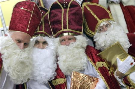 Men dressed as Santa Claus pose in the assembly hall after a meeting of the rent-a-Santa Claus service organised by the ''jobcafe.de'' at Munich's Universitiy November 23, 2009. REUTERS/Michael Dalder