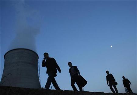People walk on a street past a power plant's cooling tower in Yingtan, Jiangxi province December 11, 2008. Picture taken December 11, 2008. REUTERS/Stringer