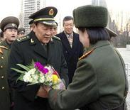 <p>Министр обороны КНР Лян Гуанле (второй слева) получает цветы от военнослужащей из КНДР после прибытия в аэропорт Пхеньяна 23 ноября 2009 года. Китай и находящаяся в международной изоляции Северная Корея должны укрепить военные связи, заявил во вторник китайский министр обороны Лян Гуанле. REUTERS/KCNA</p>