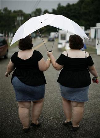 Identical twin sisters Connie (R) and Kendra Millar from Niagra Falls, Ontario, walk under matching umbrellas during the final day of the 32nd annual Twins Days Festival in Twinsburg, Ohio August 5, 2007. REUTERS/Jason Reed
