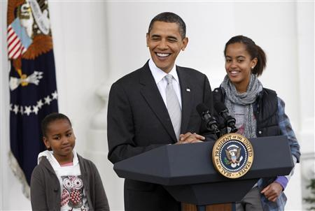 U.S. President Barack Obama speaks alongside his daughters Sasha (L) and Malia, during a turkey pardoning ceremony for ''Courage'', the National Thanksgiving Turkey, on the North Portico of the White House in Washington, November 25, 2009. REUTERS/Jason Reed