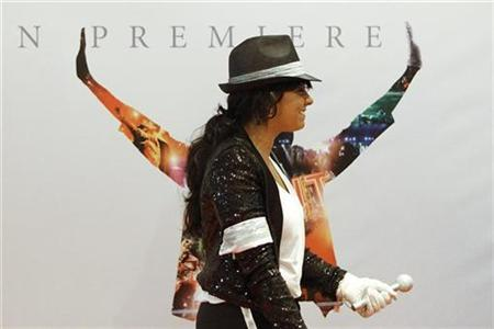 A Michael Jackson fan walks next to a poster at the Australian premiere of the documentary ''This Is It'', in Sydney October 28, 2009. REUTERS/Daniel Munoz