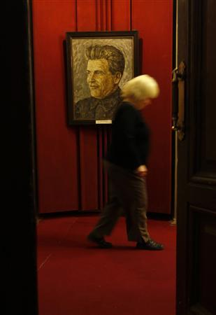 A woman passes by a portrait of Sergei Kirov, a prominent early Bolshevik leader in the Soviet Union, in the Sergi Kirov Museum in St.Petersburg December 1, 2009. Russia's Federal Security Service on Tuesday opened its archive file on the 1934 assassination case of Kirov. REUTERS/Alexander Demianchuk
