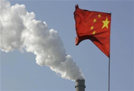 Smoke rises from a chimney of a power plant near a Chinese national flag in Taiyuan, Shanxi province December 2, 2009. REUTERS/Stringer