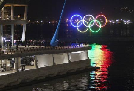 The Olympic Rings are lit up in the water of Coal Harbour on the waterfront in Vancouver, British Columbia November 4, 2009. REUTERS/Andy Clark/Files