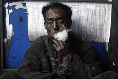 A miner smokes a cigarette during a break at a coal mine in Changzhi, Shanxi province November 25, 2009. REUTERS/Stringer