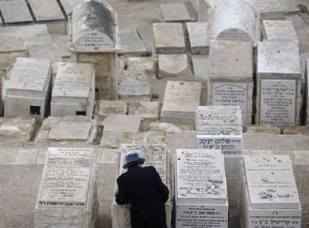 An ultra-Orthodox Jew stands near a grave at the Jewish cemetery on the Mount of Olives in Jerusalem December 7, 2009. Israel's mayor of Jerusalem called on the European Union on Monday to reject any future division of the holy city between Israel and the Palestinians. REUTERS/Ammar Awad