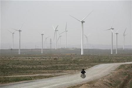 A resident rides a motor bike past the Helanshan Wind Power Plant in Wuzhong, Ningxia province, September 23, 2009. Chinese President Hu Jintao on Tuesday promised to put a ''notable'' brake on the country's rapidly rising carbon emissions, but dashed hopes he would unveil a hard target to kickstart stalled climate talks. REUTERS/Stringer