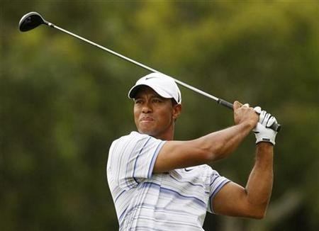Tiger Woods of the U.S. takes an approach shot on the 14th hole during the third round of the Australian Masters golf tournament in Melbourne November 14, 2009. REUTERS/Mick Tsikas