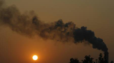 Smoke emits from a chimney of a sugar mill near Vapi, about 200 km (125 miles) north of Mumbai, November 25, 2009. REUTERS/Arko Datta