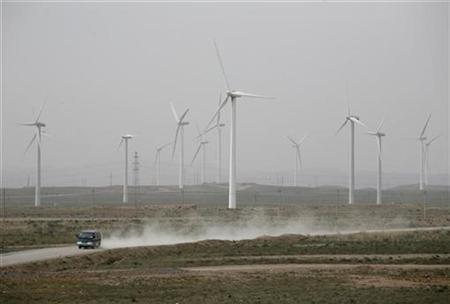 A car drives past the Helanshan Wind Power Plant in Wuzhong, Ningxia province, September 23, 2009.REUTERS/Stringer