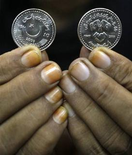 A bank employee, with her fingers stained by henna, displays 10 Pakistani Rupees ($ 0.1) coins for a photograph in Karachi October 1, 2009. Pakistan is in talks with China on a currency-swap deal with the aim of conserving its foreign exchange reserves, a senior Pakistani finance official said on Wednesday. REUTERS/Athar Hussain/Files