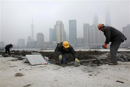 Migrant labourers work at a construction site near The Bund on the banks of the Huangpu River in Shanghai December 9, 2009. REUTERS/Aly Song