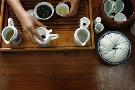 A woman prepares ''Bao Zhong'' tea using a traditional tea set in Pinglin September 27, 2007. REUTERS/Nicky Loh (TAIWAN)