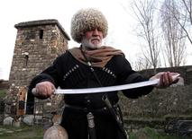 "<p>Adam Satuyev, founder of the ""Donde-Yurt"" ethnographic museum, demonstrates the use of a sabre as he stands in front of his museum in Urus-Martan, Chechnya, December 4, 2009. REUTERS/Stringer</p>"