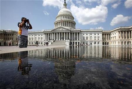 A tourist is reflected in water as he takes pictures on Capitol Hill in Washington, August 25, 2009. REUTERS/Jim Young