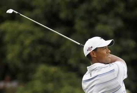 Tiger Woods of the U.S. takes an approach shot on the second hole during the third round of the Australian Masters golf tournament in Melbourne November 14, 2009. REUTERS/Mick Tsikas