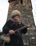"""<p>Adam Satuyev, fundador del museo etnográfico """"Donde-Yurt"""", con un hacha en frente de su museo en Urs-Martan, Rusia, dic 4 2009. Usando un gorro peludo de lana blanca y una barba de características similares, el fundador de un museo Adam Satuyev dijo que Chechenia está viviendo una reactivación cultural tras décadas de guerra. REUTERS/Stringer</p>"""