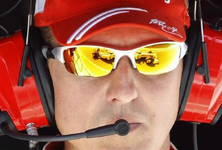 Former Ferrari Formula One driver Michael Schumacher of Germany looks at a Brawn GP team car at the pit area during the third practice session for the European F1 Grand Prix in Valencia August 22, 2009.  REUTERS/Albert Gea/Files