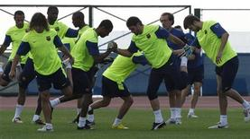 <p>Jogadores do Barcelona fazem alongamento durante treino em Abu Dhabi. Lionel Messi pode ficar de fora da estreia do Barcelona na Copa do Mundo de Clubes da Fifa contra o mexicano Atlante, campeão da Concacaf, na quarta-feira, devido a uma lesão no tornozelo.14/12/2009.REUTERS/Fadi Al-Assaad</p>