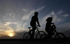 <p>A man and a child ride their bikes along a pier at St Kilda beach in Melbourne August 3, 2009. St Kilda beach is Melbourne's most famous beach, 6 km (3.7 miles) south of the central business district. REUTERS/Mick Tsikas</p>