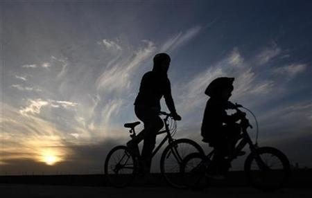 A man and a child ride their bikes along a pier at St Kilda beach in Melbourne August 3, 2009. St Kilda beach is Melbourne's most famous beach, 6 km (3.7 miles) south of the central business district. REUTERS/Mick Tsikas