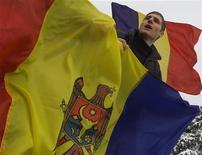 <p>Румынский студент держит в руках флаг Молдавии на акции протеста в Бухаресте 25 января 2004 года. Стремящаяся в Европу Молдавия уберет со своей границы с родственной Румынией колючую проволоку, оставшуюся в наследство от бывшего СССР. REUTERS/Bogdan Cristel</p>