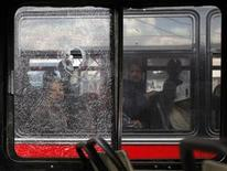 <p>Passengers on a bus look at a slain assailant through the windows of another bus in Guatemala City March 24, 2009. REUTERS/Daniel LeClair</p>