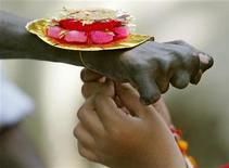 <p>A schoolgirl ties a Rakhi on the wrist of a leprosy-affected patient in the northeastern Indian city of Siliguri August 9, 2006. REUTERS/Rupak De Chowdhuri</p>