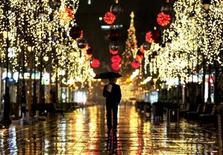 <p>A man walks near trees illuminated with Christmas lights in Skopje December 14, 2009 REUTERS/Ognen Teofilovski</p>